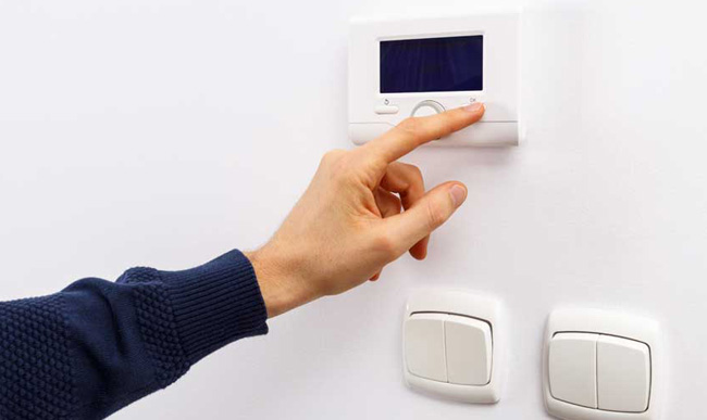Finger switching off switches on a white wall.
