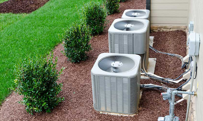 Heat pumps installed on the ground of green backyard