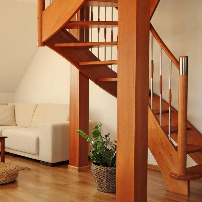 Modern bespoke wooden staircases and beige coloured sofa.