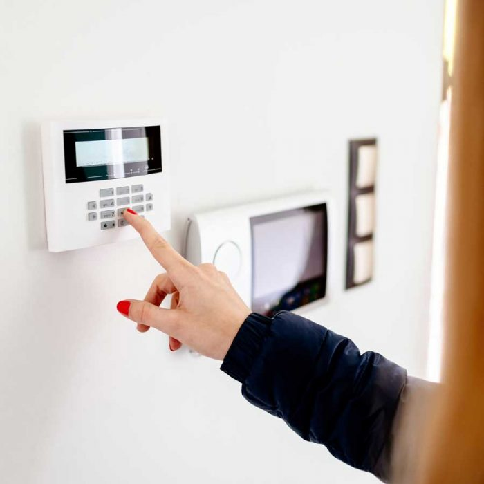 Woman operating home security system installed by TEL Constructions