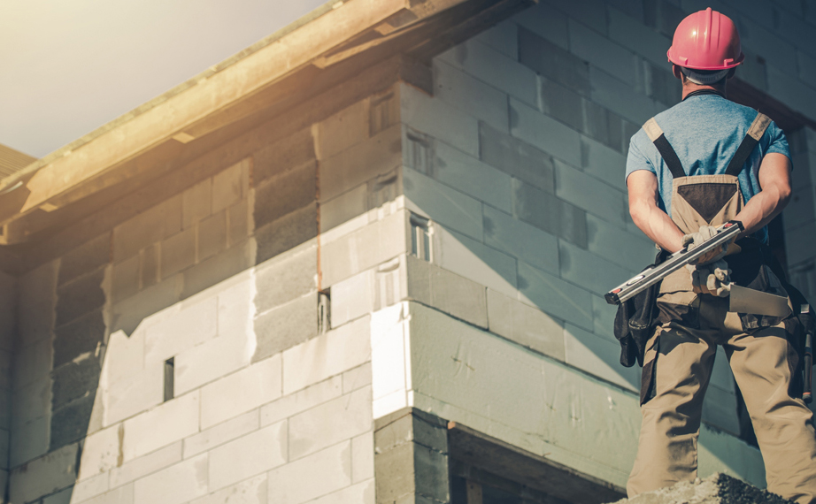 Construction worker near an under-constructed pitched roof house.